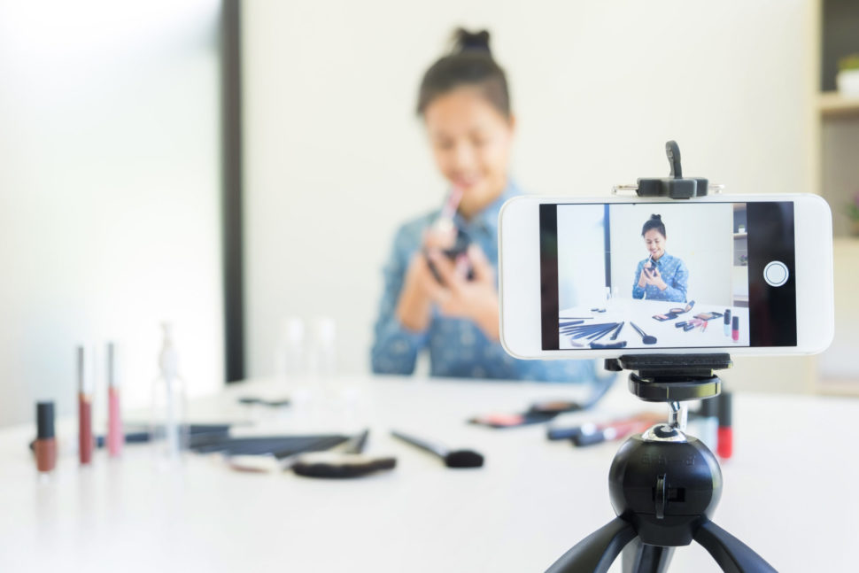 A young professional using her smartphone to live stream | Indypendenz | Shutterstock.com