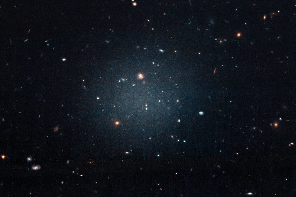 "This large, fuzzy-looking galaxy is so diffuse that astronomers call it a ""see-through"" galaxy because they can clearly see distant galaxies behind it. The ghostly object, catalogued as NGC 1052-DF2, doesn't have a noticeable central region, or even spiral arms and a disk, typical features of a spiral galaxy. But it doesn't look like an elliptical galaxy, either. Even its globular clusters are oddballs: they are twice as large as typical stellar groupings seen in other galaxies. All of these oddities pale in comparison to the weirdest aspect of this galaxy: NGC 1052-DF2 is missing most, if not all, of its dark matter. 