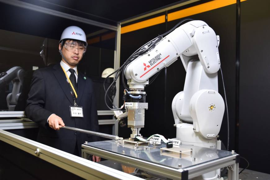 A Mitsubishi Electric Corp. engineer operates a robotic arm during a research and development open house event in Tokyo on Wednesday. | Mitsubishi Electric Corporation