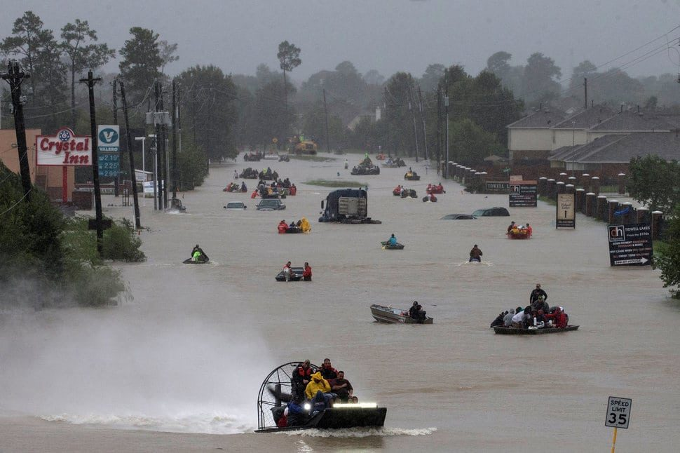 Residents use boats to evacuate flood waters from Tropical Storm Harvey along Tidwell Road east Houston, Texas, U.S. August 28, 2017. REUTERS/Adrees Latif