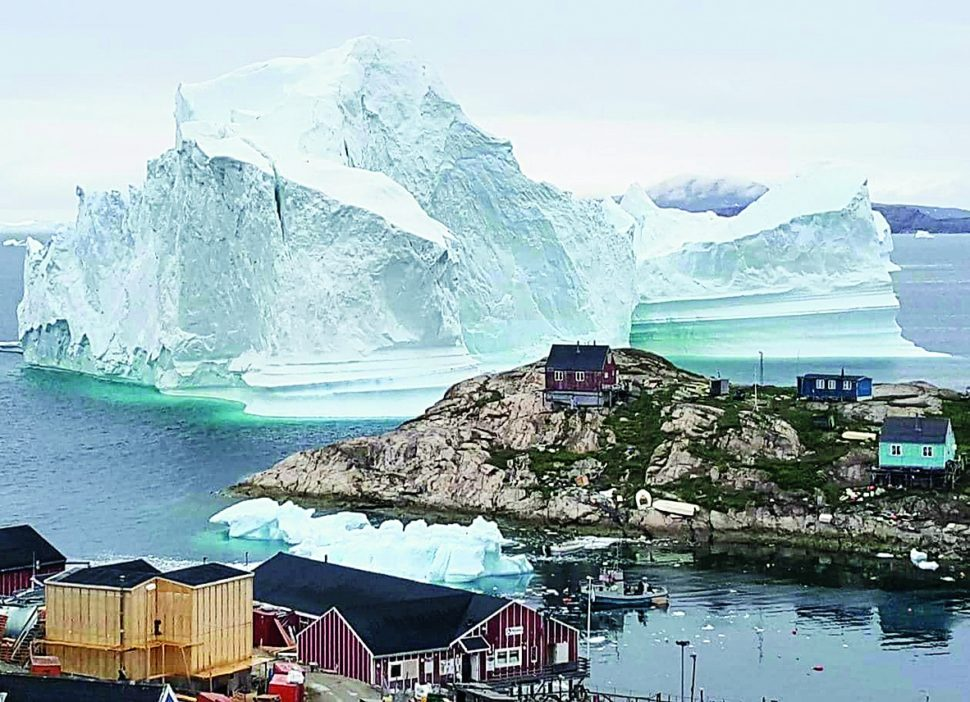 An iceberg is seen behind an Innaarsuit settlement, Greenland.  | Photo courtesy of Reuters
