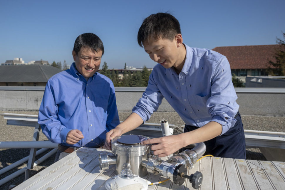 Professor Shanhui Fan and postdoctoral scholar Wei Li atop the Packard Electrical Engineering building with the apparatus that is proving the efficacy of a double-layered solar panel. The top layer uses the standard semiconductor materials that go into energy-harvesting solar cells, the novel materials on the bottom layer perform the cooling task. | Image credit: L.A. Cicero