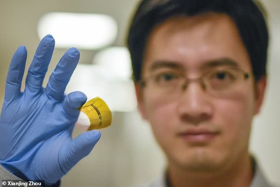 Xu Zhang holding the WiFi signal-harvesting device that he and his colleagues developed | MIT