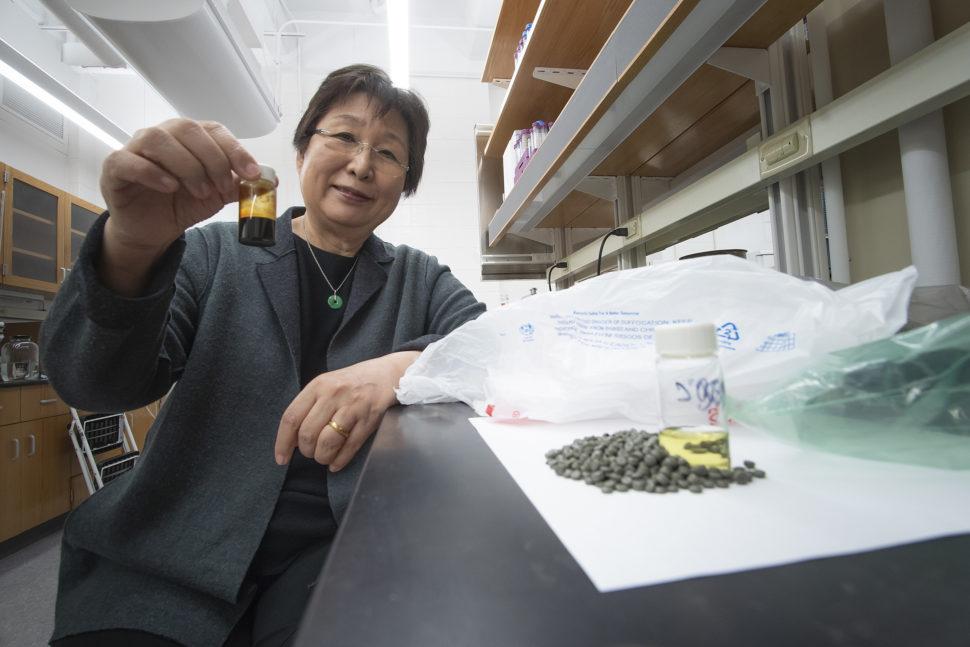 Linda Wang holding a bottle of oil made using a new waste conversion technology that transforms plastic waste into oil | Purdue Research Foundation/Vincent Walter
